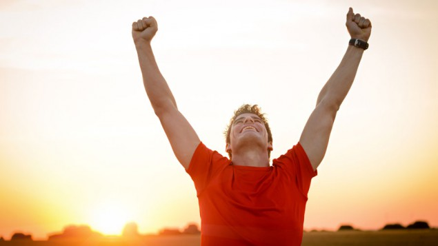 a man in a red t-shirt throwing his hands up in victory, with a sunset behind him