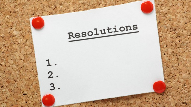 A list of blank New Years resolutions pinned onto a cork board.