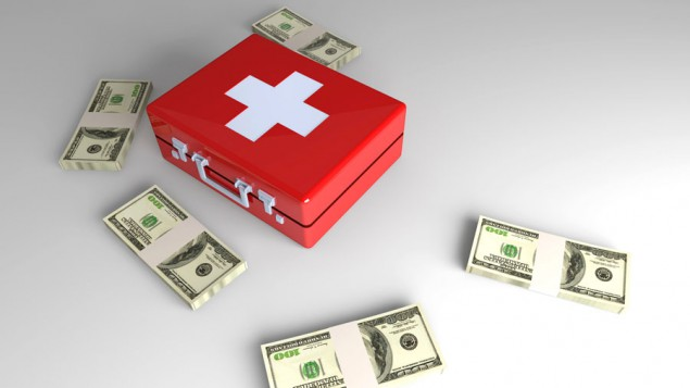 a white table with stacks of $100 dollar bills and a red and white first aid kit