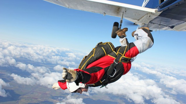 a man jumping out of a plane with a red sky diving outfit