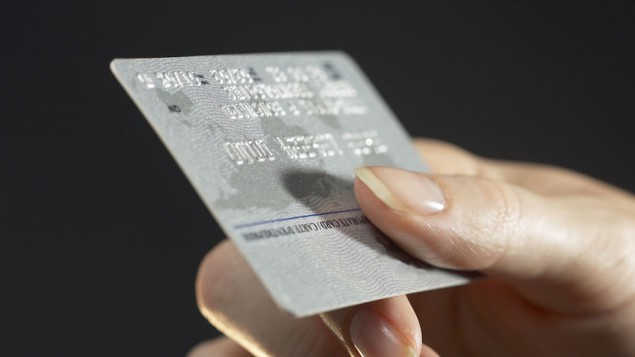 a hand holding up a silver credit card, against a black background