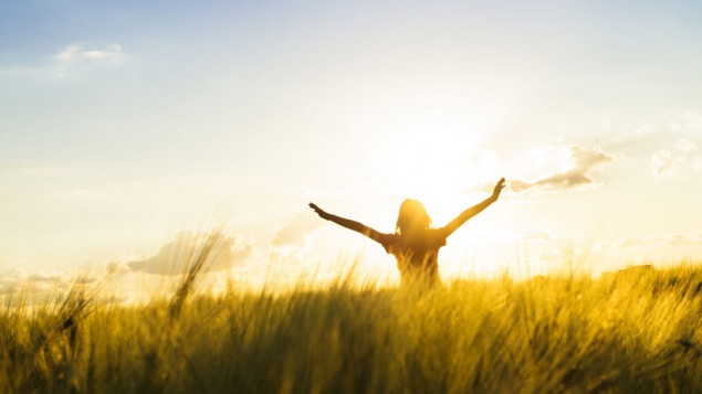 a woman standing in a field with long grass, and she's looking at the sun and raising her arms in the air
