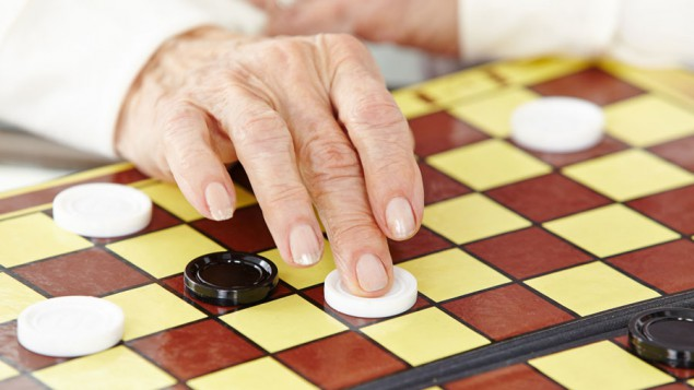 the hand of an old woman moving a white checkers piece on a yellow-and-brown checkerboard, amidst other white and black checker pieces