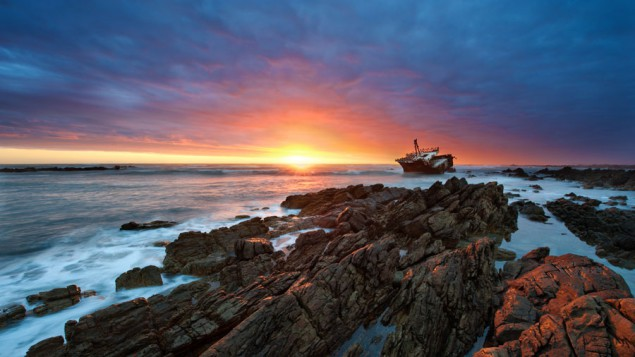 rocks jutting out of the surf on the edge of the ocean, at sunset, and in the distance there's a ship stuck on the rocks