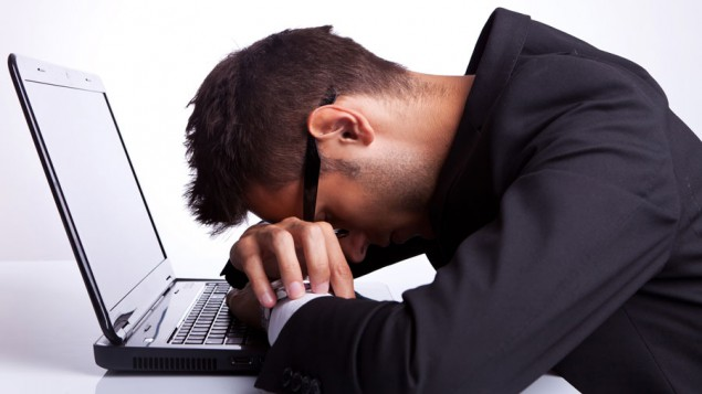 a business man sitting at a white desk with a black laptop, and he has his hands on the keyboard of the laptop, and he's resting his head on his hands
