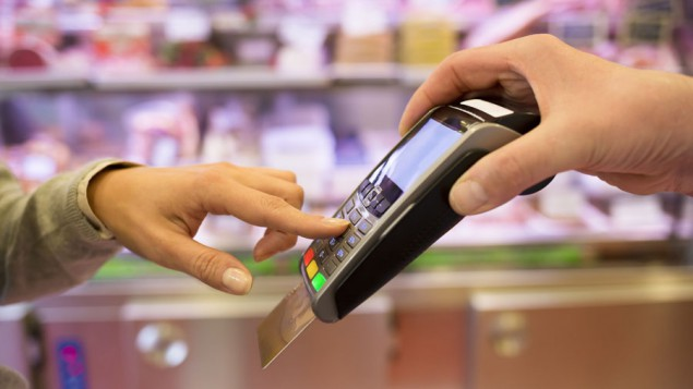 the hand of a young woman pressing the buttons on a portable credit card payment device being held by a store clerk