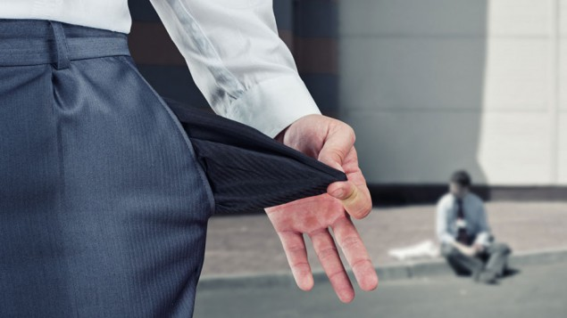 close-up of a business man pulling out the inside of his pants pocket to show that it's empty, and a blurred background showing a business man sitting on the sidewalk outside an office building