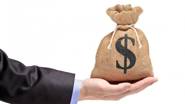 the hand of a business man holding a full gunny sack marked with a dollar sign, against a white background