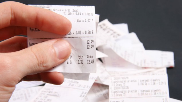 a hand holding up a receipt to see the total amount spent, with a blurred pile of receipts on a table in the background
