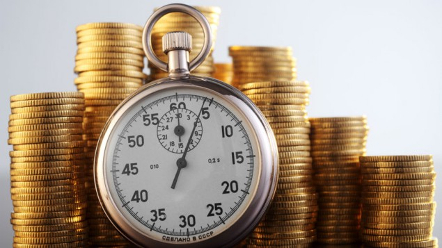 a silver stopwatch resting against stacks of gold coins