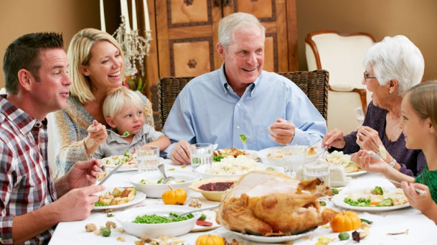 a family of grandparents, parents and grandchildren eating a feast