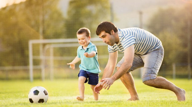 a father playing soccer with his young son on a soccer field