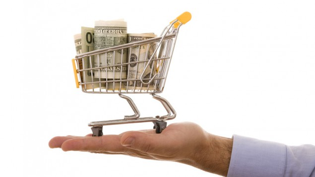 a businessman's hand holding up a mini shopping cart full of various dollar bills; against a white background