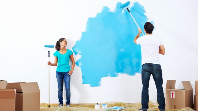 a young man painting a white wall with blue paint, while his wife holds another paint roller and watches, and the floor is covered in moving boxes and paint tarps