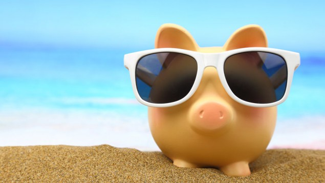 a yellow piggy bank with sunglasses sitting in the sand with a blurred image of an ocean in the background