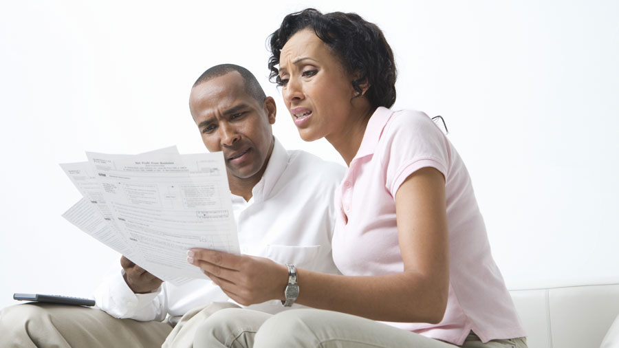 couple sitting on a white leather couch looking at tax documents with worried expressions on their faces