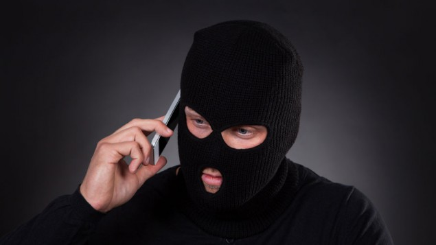 a thief wearing a black shirt and black ski mask, talking on a cellphone