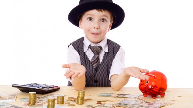 a little boy dressed in a fancy clothes, sitting at a wooden table with a calculator, red piggy bank, various dollar bills and coins; and he's lifting up his hands as if questioning something
