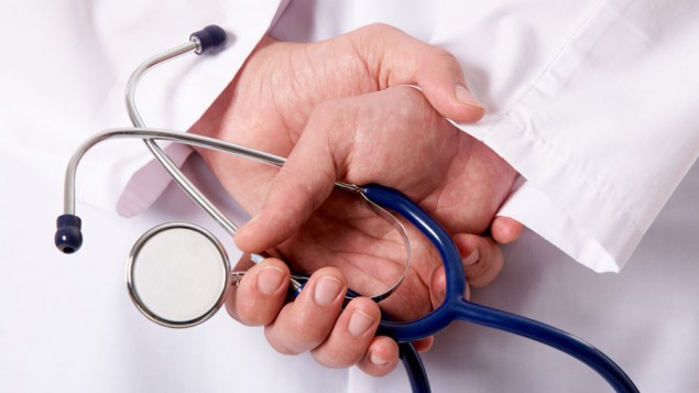 a doctor's hands held behind his back, and one of his hands is holding a blue and silver stethoscope