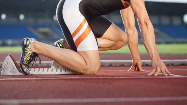 a runner kneeling down and taking his stance at the start line of a track