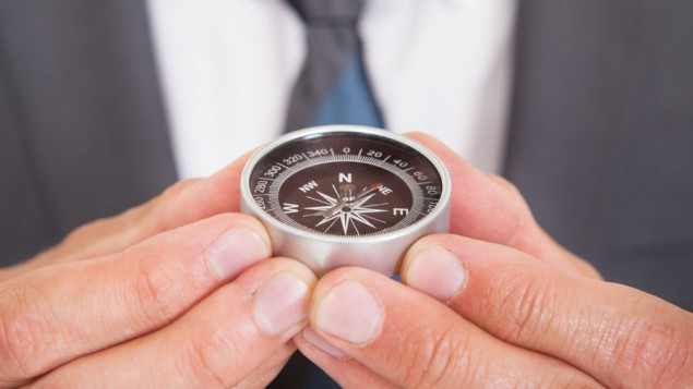 a business man holding up a tiny compass