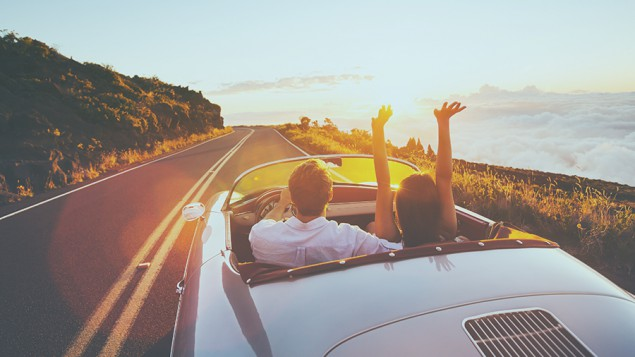a young man driving a convertible and a woman sitting in the passenger seat with her hands in the air, and they're on a road on the edge of the mountain with a sunset in the distance