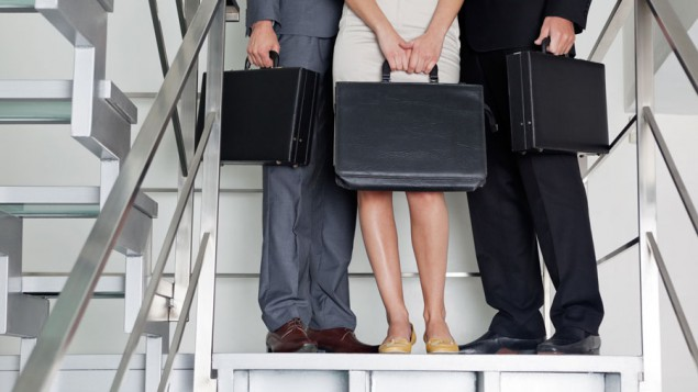 two business men and a business woman, each holding their own black briefcase, standing on a flight of stairs