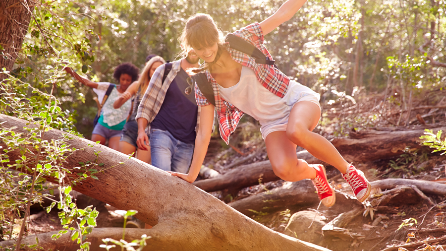 four teenagers going on a hike in the woods, and the girl leading the group is jumping over a fallen tree