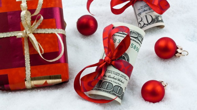 a gift with red wrapping paper, red ornaments, and rolls of money wrapped with red ribbon, laying in fake snow