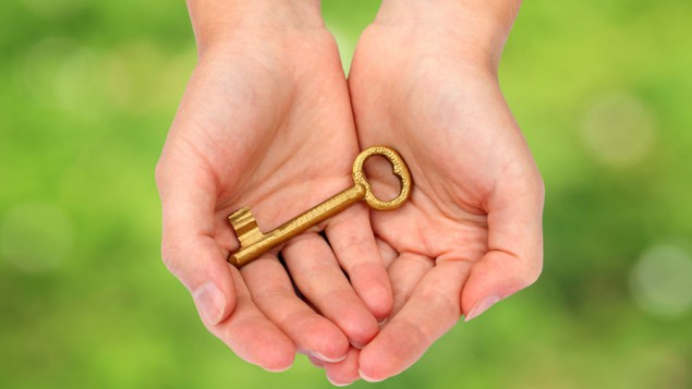 two hands holding a gold key