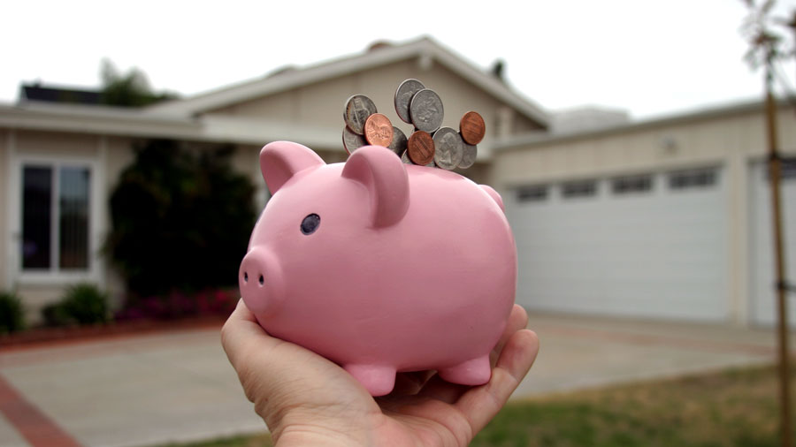 a hand holding a piggy bank with coins in front of a house