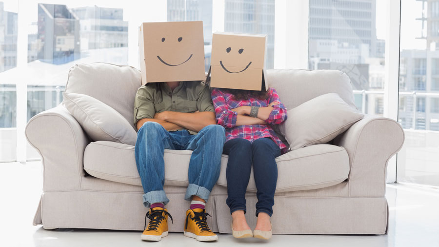an angry couple sitting on a couch with cardboard boxes over their heads that have drawn-on smiley faces