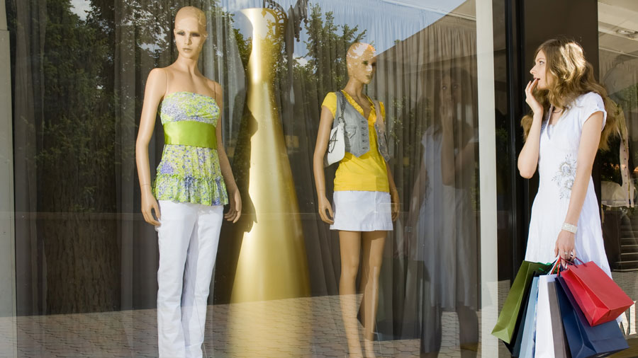 a woman with shopping bags looking at dressed mannequins in a store window