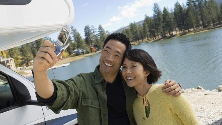 couple posing for a selfie in front of a lake in the mountains