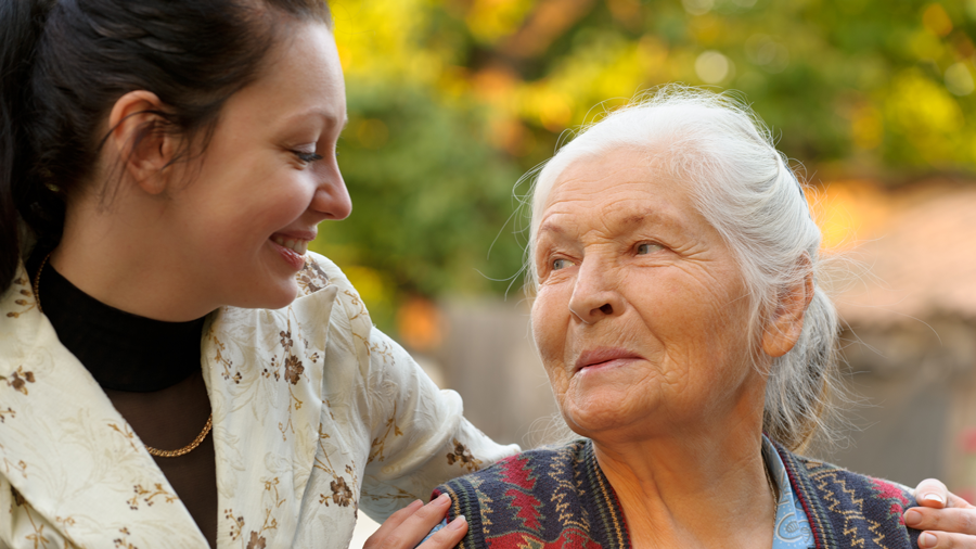 a young woman smiling and putting her arm around the shoulders of an elderly woman