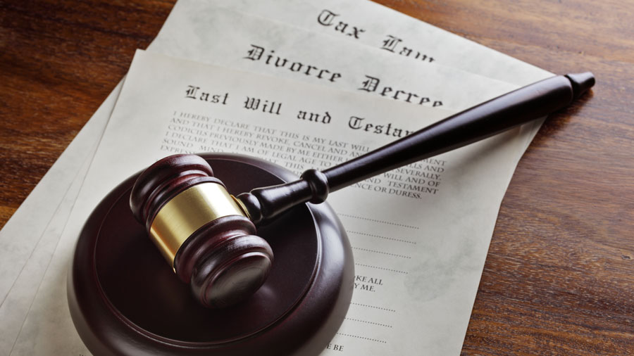a gavel on top of a last will and testament, divorce decree, and tax document, on a wooden table