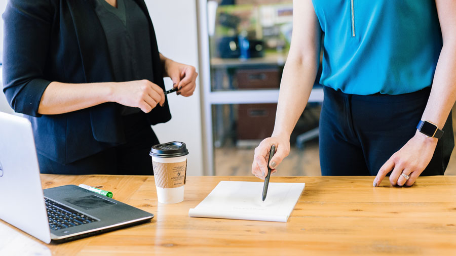 business woman with a black shirt and skirt talking to another business woman wearing a blue shirt and black skirt, holding pens and looking at a note pad on a wooden table with a cup of coffee and laptop in the foreground