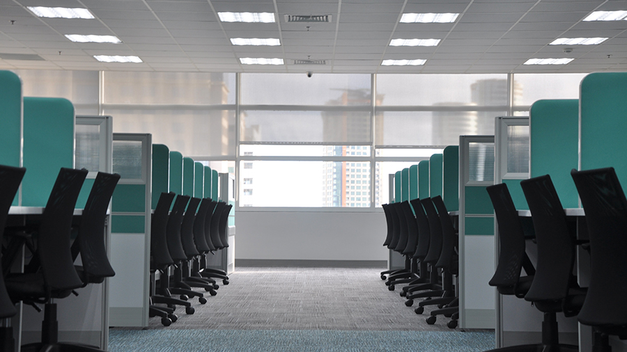 an empty office with black chairs and green window dividers